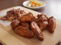 Fried Chicken Wings Covered i riktig varm BBQ-s?s med en sida av Cole Slaw Carrots och selleri tj?nade som p? en sk?rbr?da royaltyfri foto