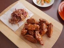 Fried Chicken Wings Covered i riktig varm BBQ-s?s med en sida av Cole Slaw Carrots och selleri tj?nade som p? en sk?rbr?da royaltyfri bild