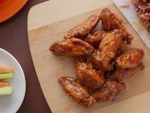Fried Chicken Wings Covered i riktig varm BBQ-s?s med en sida av Cole Slaw Carrots och selleri tj?nade som p? en sk?rbr?da arkivbild