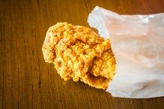 Fried Chicken Wings en bolsa de papel en la tabla de madera Imagen de archivo libre de regalías