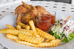 Fried chicken wings and french fries. Fried chicken wings with french fries on the table Royalty Free Stock Photography