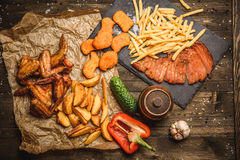 Fried chicken wings with French fries. And vegetables on wooden background Royalty Free Stock Photography