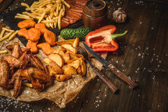 Fried chicken wings with French fries. And vegetables on wooden background Royalty Free Stock Photo