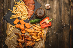 Fried chicken wings with French fries. And vegetables on wooden background Stock Images