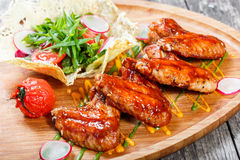 Fried chicken wings with fresh salad, grilled vegetables and bbq sauce on cutting board on wooden background close up Stock Images