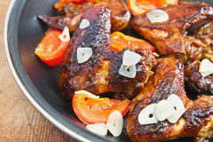 Fried chicken wings with garlic and tomatoes. Into the pan Stock Photos