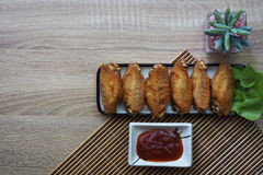 Fried chicken wings in a square dish, placed on a brown wooden floor. And have ketchup next to it. copy space Royalty Free Stock Photos