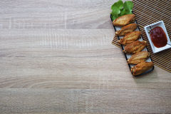 Fried chicken wings in a square dish, placed on a brown wooden floor. And have ketchup next to it. copy space Stock Images