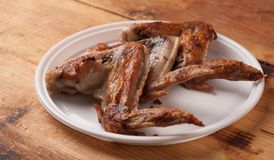 Fried chicken wings in a white plastic plate on the wooden table,. Junk food Stock Image