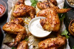 Fried chicken wings with white sauce. Close up view Royalty Free Stock Images