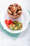 Fried chicken wings and zucchini, pepper. Fried chicken wings and zucchini, pepper on a white plate Stock Photo