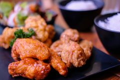 Fried chickens and two bowls of rice. On wooden table royalty free stock photography