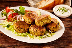 Fried chickpea and fava bean patties. Or falafel, served on a large platter with fresh salad and sour cream for tasty Turkish cuisine Royalty Free Stock Image