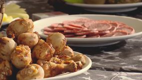Fried chiken legs on a plate focus in, plate fool of salami focus in on a table stock video