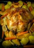 Fried chiken med grönsaker på en panna på en svart trätabell T Royaltyfri Bild