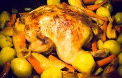 Fried chiken med grönsaker på en panna på en svart trätabell T Royaltyfri Fotografi