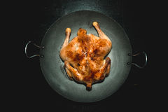 Fried chiken on a pan on a black wooden table. Toned Royalty Free Stock Photo