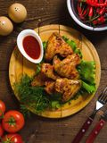 Fried chiken wings on wooden plate. dark table royalty free stock image