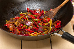 Fried chili pepper and vegetable on a wok pan stock image