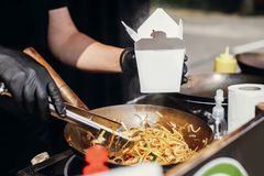 Fried chinese japanese noodles with vegetables and shrimps in takeaway box.Food delivery. Chef putting noodles in carton box to go. From open kitchen. Asian royalty free stock photos