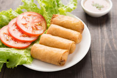 Fried Chinese traditional spring rolls on wooden background. Royalty Free Stock Images