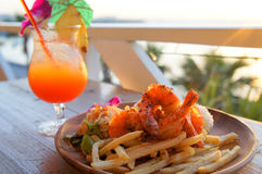 Fried chips with shrimps and juicy fruit in resort royalty free stock image