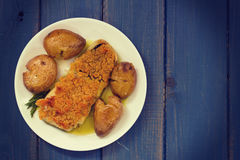 Fried cod with bread and potato on dish. On blue background Stock Photo