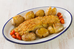 Fried cod with bread and potato on dish Stock Image