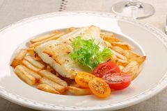 Fried cod fillet on a white plate and french fries.  Stock Photo