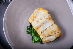 Fried cod fillets and spinach. On a plate Stock Photos
