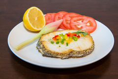 Fried cod fillets and vegetables. On the table Stock Photography