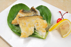 Fried cod. Fish with lemon and vegetables Stock Photos
