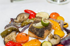 Fried cod with roasted vegetables. Fried cod with roasted vegetables on a plate Stock Image