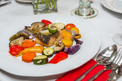 Fried cod with roasted vegetables. Fried cod with roasted vegetables on a plate Stock Photos