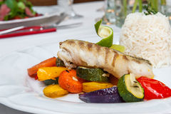 Fried cod with roasted vegetables. Fried cod with roasted vegetables and rice Stock Photos