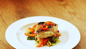 Fried cod. With Savoy cabbage roasted red pepper and port sauce royalty free stock photo
