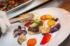 Fried cod with vegetables. Hand of cook preparing lunch. Fried cod with roasted vegetables Royalty Free Stock Photo