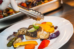 Fried cod with vegetables. Hand of cook preparing lunch. Fried cod with roasted vegetables Stock Image