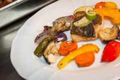 Fried cod with vegetables. Preparing fried cod with roasted vegetables Stock Image