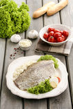 Fried cod on white plate with fresh vegetables. Top view of fried cod on white plate with fresh vegetables and egg, on old wooden table. Tomatoes and other fresh Royalty Free Stock Photography