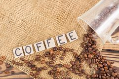 Fried coffee beans poured out of glass on hessian sack cloth beside handwritten word COFFEE laid out of square cardboard piece. Fried coffee beans on hessian royalty free stock image