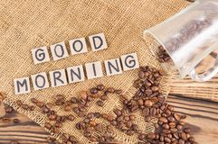 Fried coffee beans poured out of glass on hessian sack cloth beside handwritten words GOOD MORNING laid out of square cardboard pi. Fried coffee beans on hessian stock photos