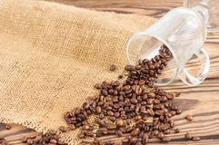 Fried coffee beans poured out of glass on hessian sack cloth. On old wooden rustic brown boards stock images