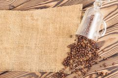Fried coffee beans poured out of glass on hessian sack cloth. On old wooden rustic brown boards stock photo
