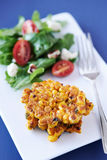 Fried Corn Fritters. Closeup of a corn fritters on plate with side salad Royalty Free Stock Photos