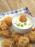Fried cornmeal-crusted chicken bites with yogurt herb dressing. Royalty Free Stock Images