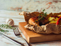 Fried crispy chicken legs with potatoes, garlic and thyme on rustic table. Stock Photography