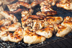 fried with a crispy golden crust fried chicken wings on the grill. Royalty Free Stock Photo