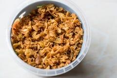 Fried Crispy Onion Flakes i plast- packebunke royaltyfria bilder