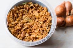 Fried Crispy Onion Flakes i plast- packebunke royaltyfri fotografi